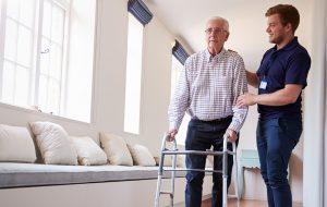 Verzorger helpt oude man met wandelrekje in zorgtehuis