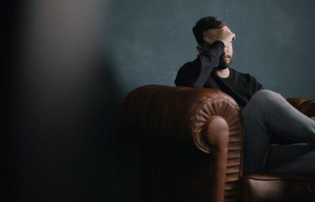 Man met werkstress zit in leren bank
