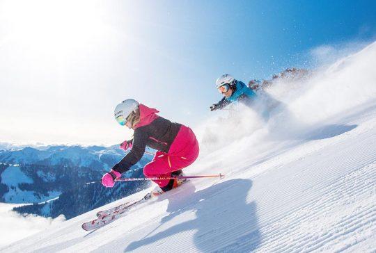 Twee personen skiën op besneeuwde bergflank.