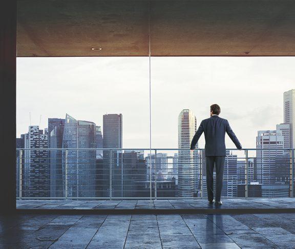 Man in pak kijkt uit op skyline van wolkenkrabbers.