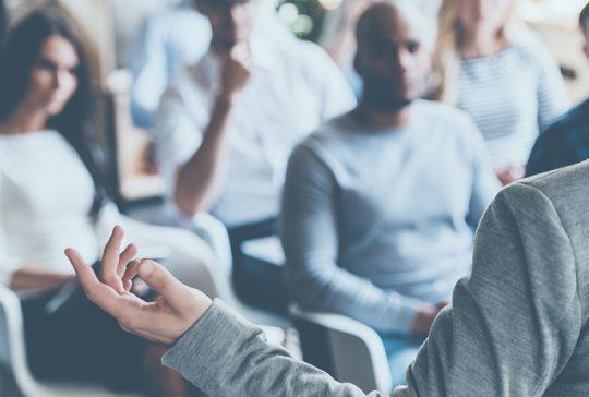 Persoon geeft presentatie aan mensen in meetingroom