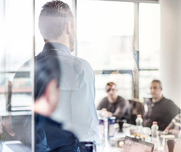 Man spreekt voor groep mensen in meetingroom