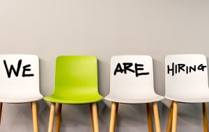 Vier lege stoelen met de tekst 'We are hiring'