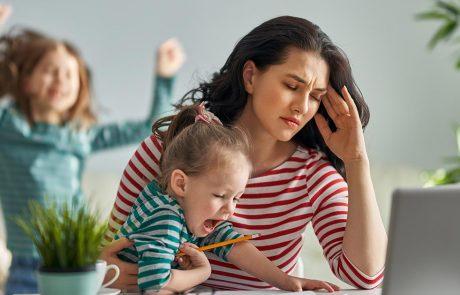 Stress bij het thuiswerken: vrouw probeert op haar laptop te werken terwijl haar twee kinderen aandacht opeisen