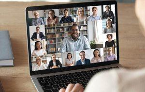 Vrouwelijke werknemer praat met collega's via videogsprek op haar laptop