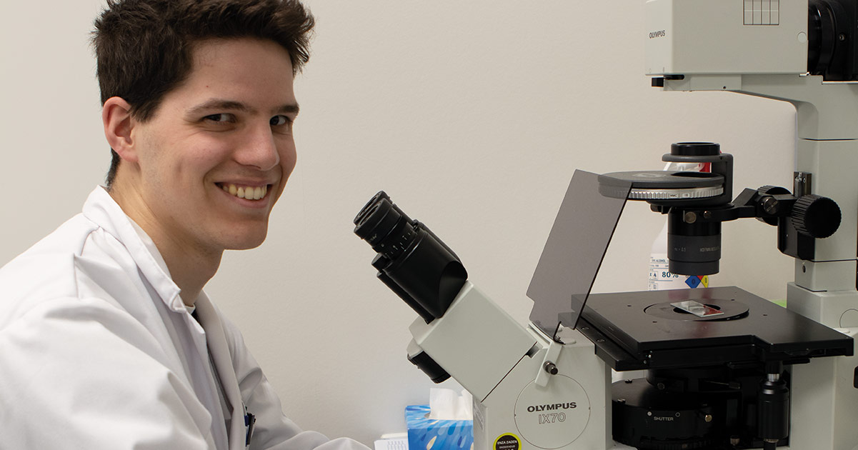 Nathan Geschiere achter microscoop