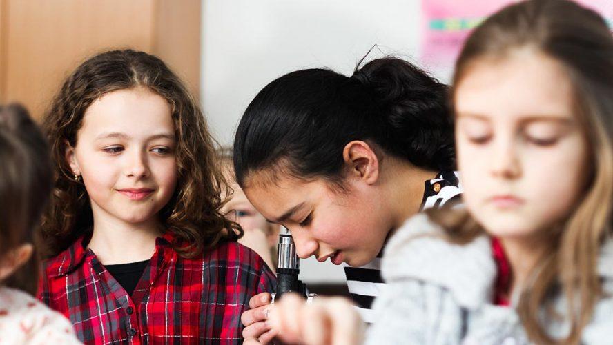 Meisjes in klaslokaal met microscoop