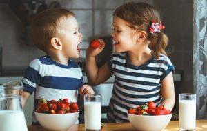 dwójka dzieci jedzących owoce