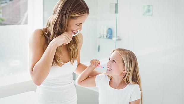 kobieta i dziewczynka myją razem zęby