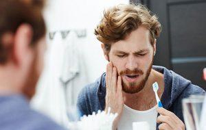 mężczyzna cierpiący na nadwrażliwość zębów