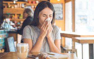 kobieta dmuchająca nos w kawiarni