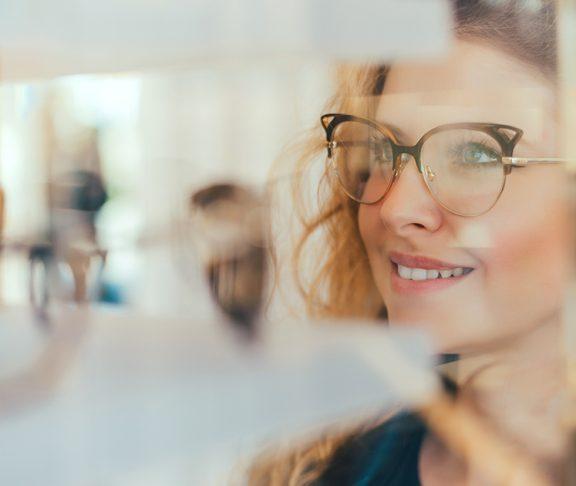 kobieta przymierzająca okulary