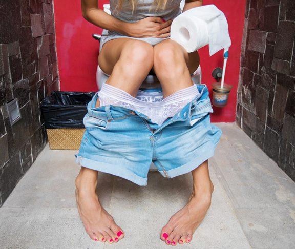 kobieta siedząca na ubikacji mająca problem z oddaniem moczu
