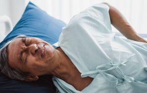 leżący mężczyzna cierpiący na ból pleców lub nerek