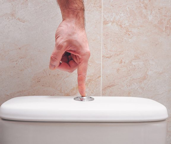mężczyzna spłukujący toaletę