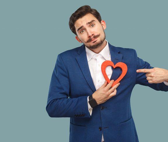 mężczyzna w garniturze z wyciętym serce z papieru