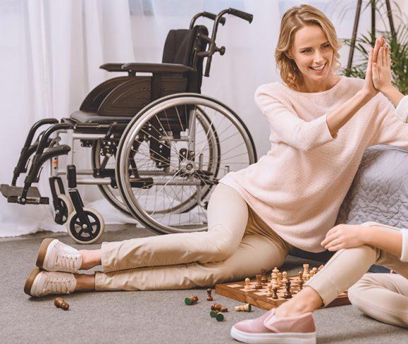 matka i córka grające w szachy w tle wózek inwalidzki
