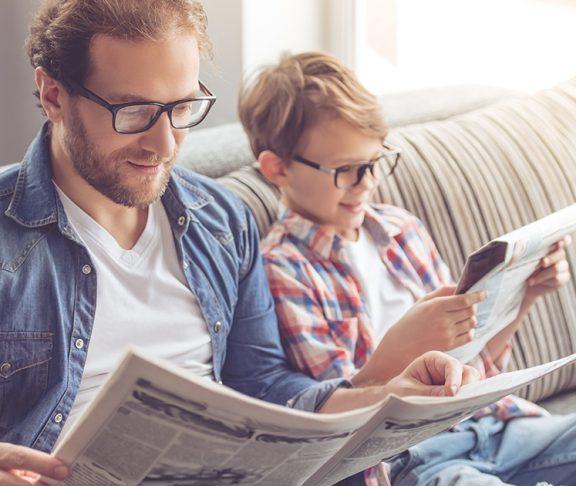 ojciec i syn w okularach czytający gazety