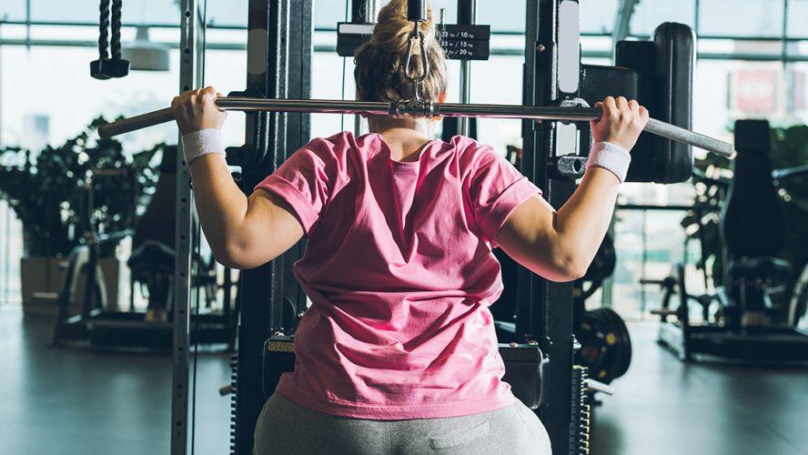 otyła kobieta ćwicząca na siłowni