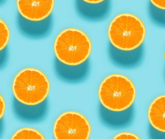 przekrojone na pół pomarańcze na niebieskim tle