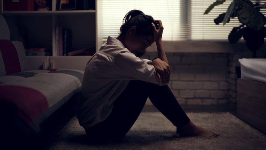 smutna kobieta siedząca w zaciemnionym pokoju