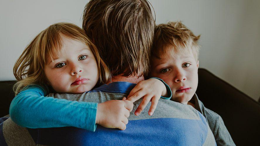 smutne dzieci przytulające się do taty