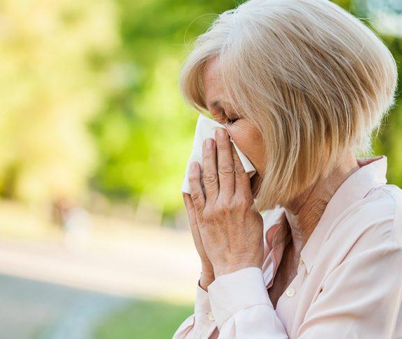 starsza kobieta wydmuchująca nos na ławce w parku