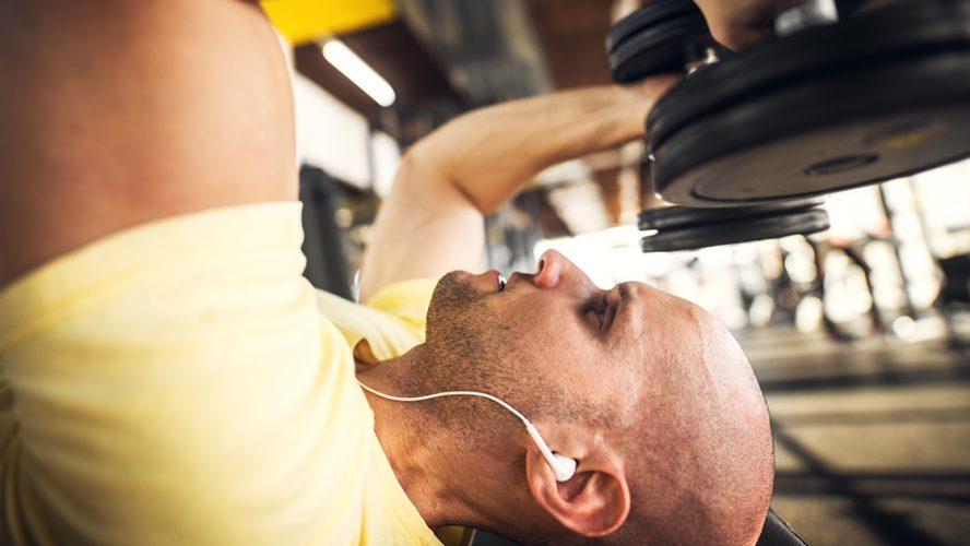 wysportowany mężczyzna z hantlami na siłowni