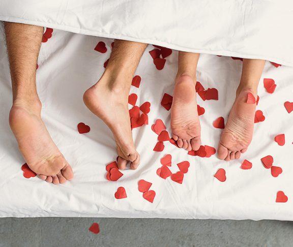 wystające spod kołdry stopy pary kochanków w pościeli usłanej sercami