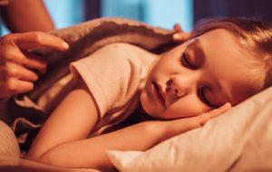 zasypiająca dziewczynka przykrywana pościelą