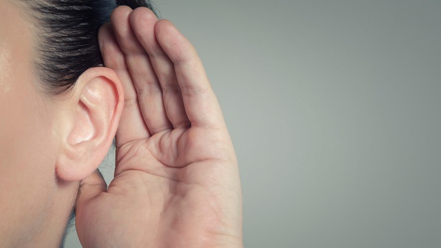 kobieta przykładająca dłoń do ucha aby więcej usłyszeć