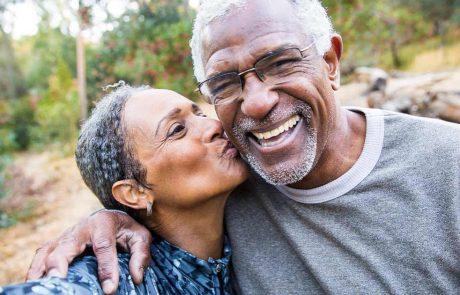 Black senior couple smiling for a kissing selfie