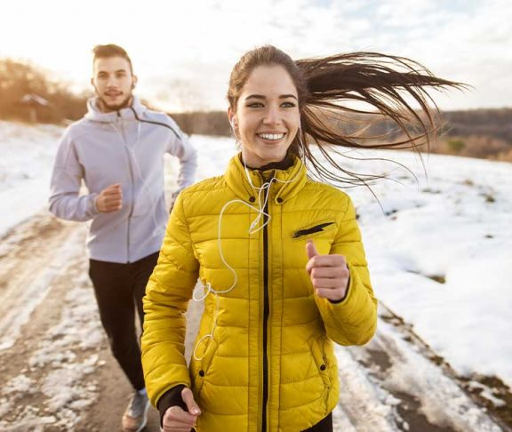 Two people happy to be running outside in the winter