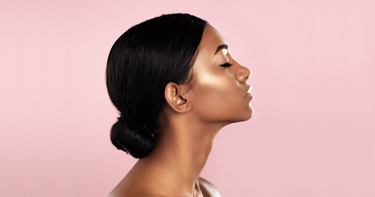 Black woman with her eyes closed, in profile against a pink background