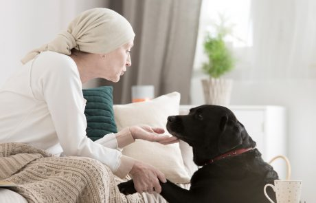 Woman with cancer patting dog