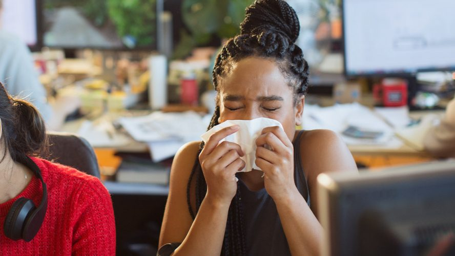 Another woman sneezing in an office