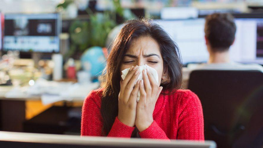 Woman sneezing in an office