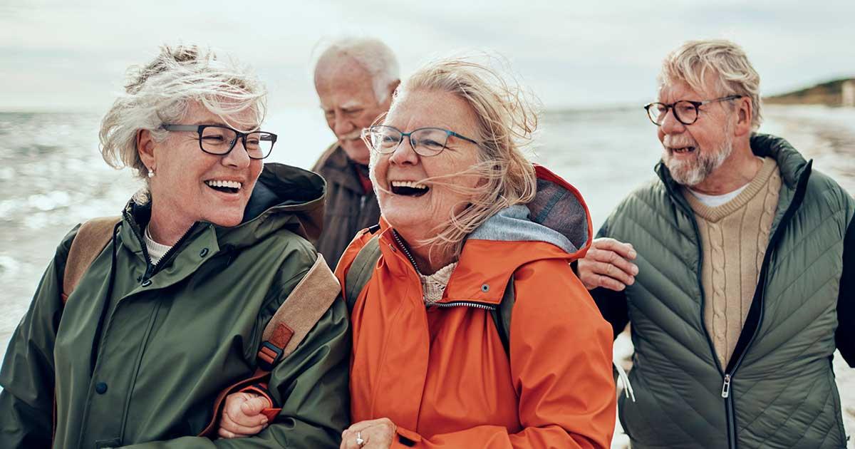 Four seniors enjoying a hike on the beach