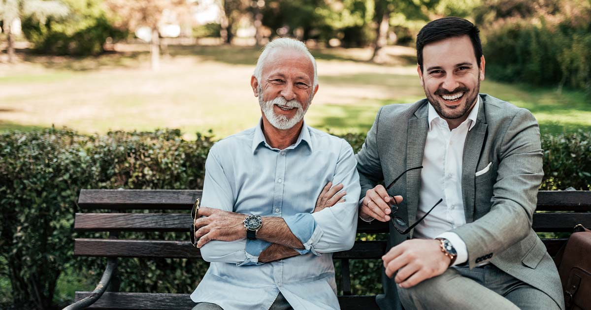 Two smiling men sitting on an outdoor bench