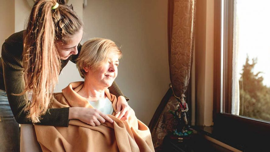 Woman helping take care of an older woman in her home