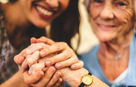 Adult and elderly women holding hands and smiling