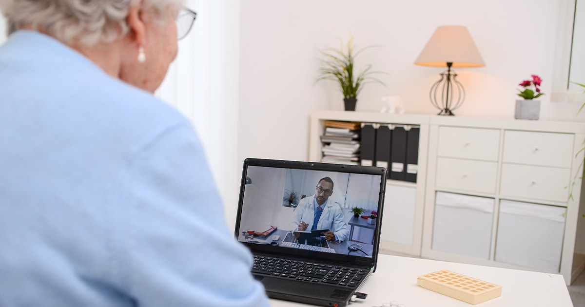 Elderly woman receiving doctor's advice through a computer chat