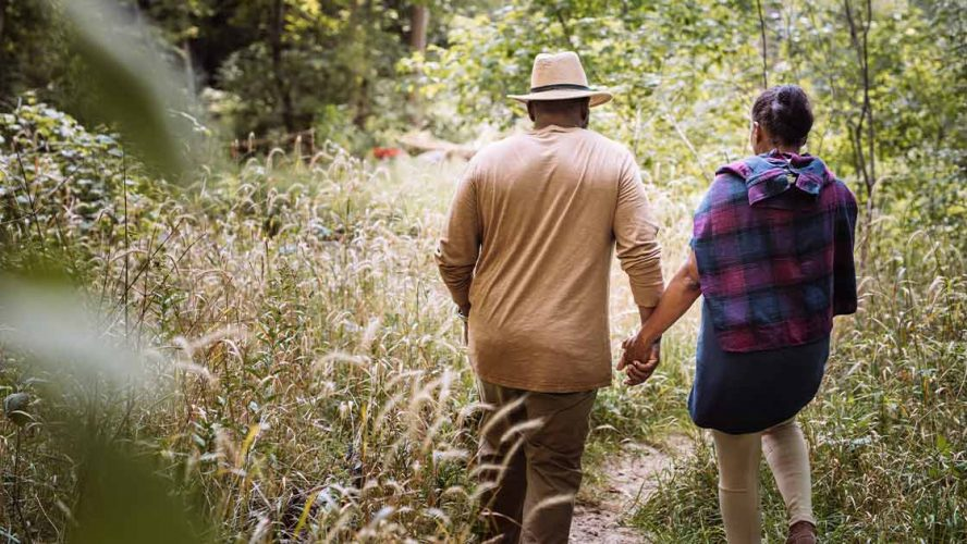 Older couple walking through a field