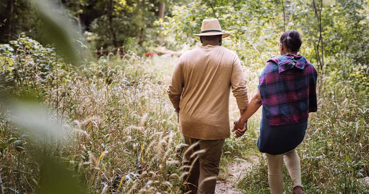 Older couple walking through a field