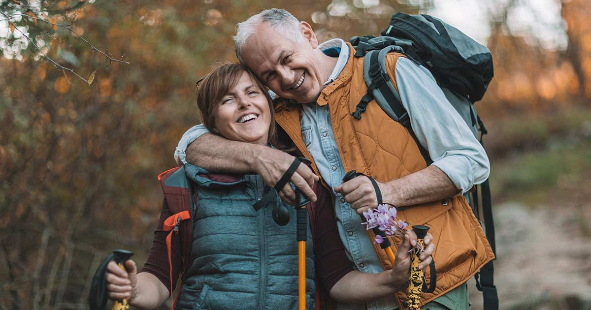 Senior couple grinning while on a hike