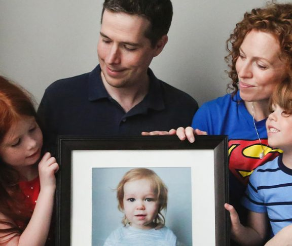 The Promoli family with a framed photograph of Jude