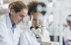 Two female scientists using a microscope