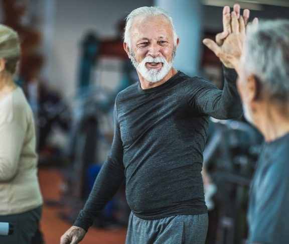 Two senior men high-fiving at the gym