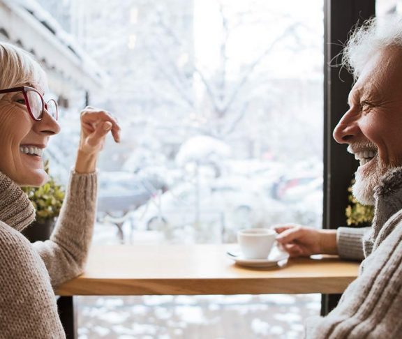 Two seniors smiling over a cup of coffee