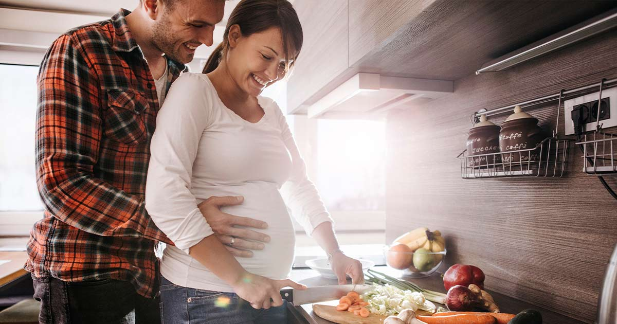 Pregnant couple making dinner in the kitchen